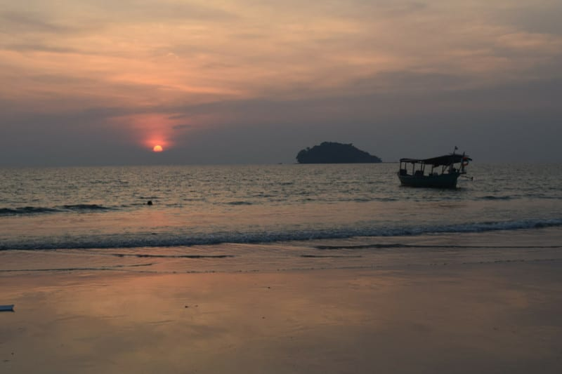 Another cambodian sunset with a boat drifting in the water
