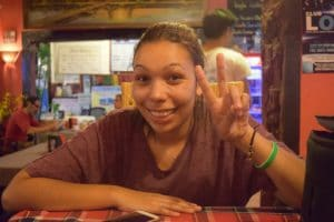 A girl making a peace sign in a cambodian restaurant