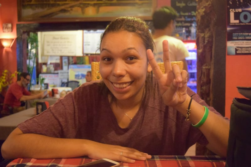 A girl making a peace sign in a cambodian restaurant backpacking Cambodia