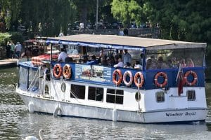 A boat saling down the thames in windsor with many people aboard taking a tour