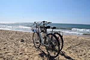 Two bikes sitting together on the sand