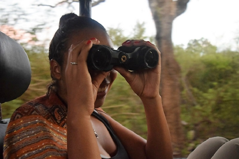 A woman holding a pair of binoculars to her face