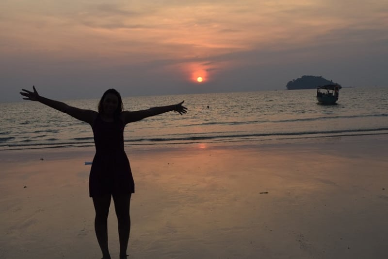 A lady being silloueted by a sunset on a cambodian beach