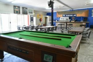 Green pool table with 2 cues and tables and chairs