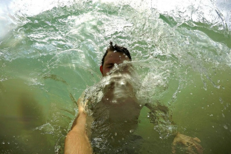 A man being hit by a wave from behind