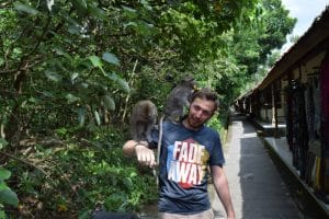 A man with 2 monkeys on his shoulder