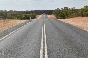 A long straight road over the hills in the Outback
