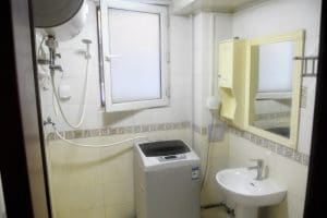 Bathroom with washing machine and sink in view