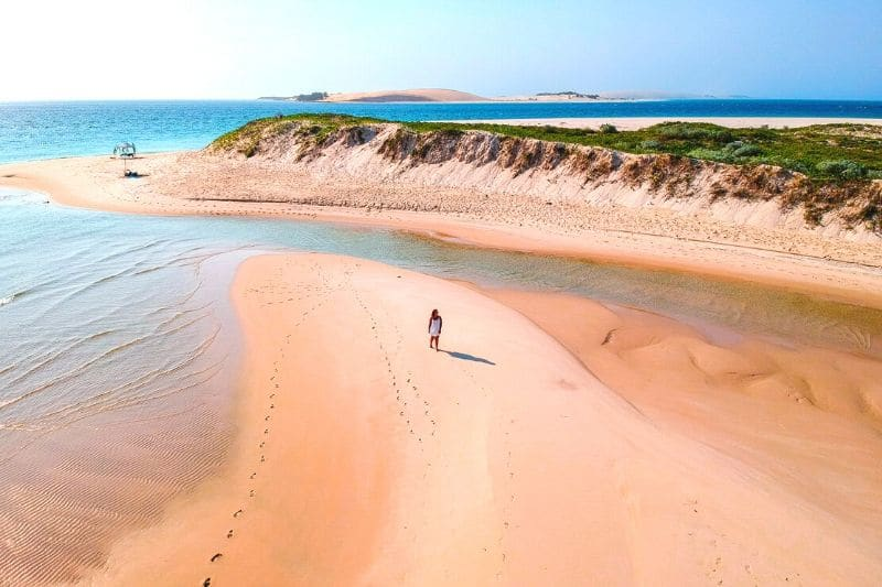 drone shot of a woman standing on the sand with small cliff behind and shalow waters surrounding her