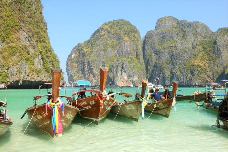 Small wooden boats with scarves tied to them waiting in the clear blue/green water