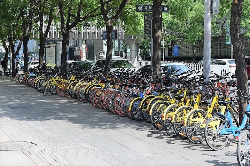 Around 100 yellow and orange bikes from the bike sharing apps Ofo and MoBike