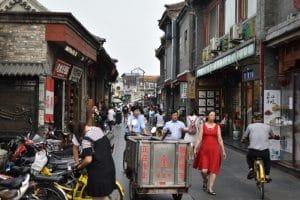 Many people down a hutong looking at shops