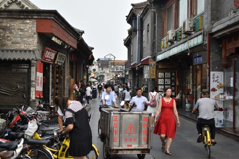 Many people down a hutong looking at shops