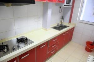 Narrow kitchen with red panelled cupboards and yellow surfaces