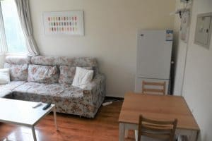 Living room with floral sofa, fridge in the corner and a wooden dining table