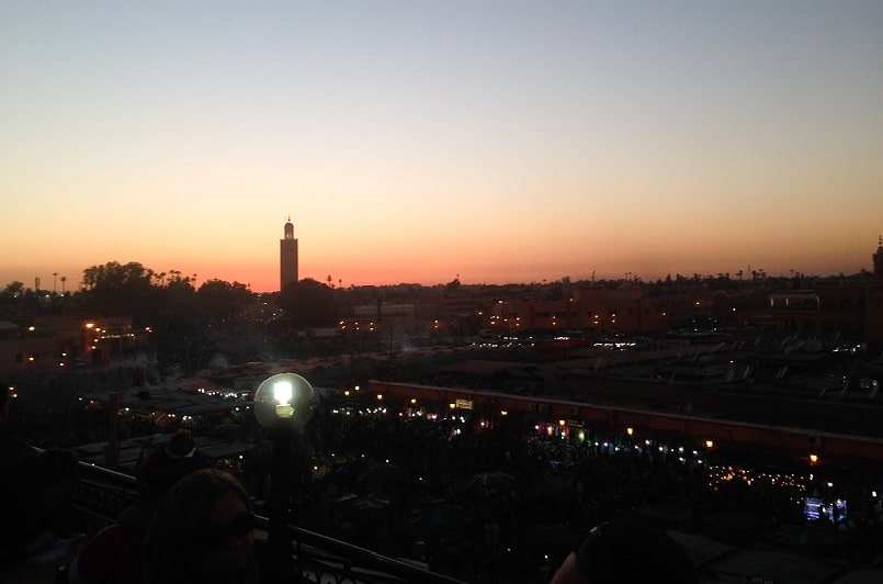 Red and orange sunset looking over the darkened city of Marrakeh with one tower visible in the background
