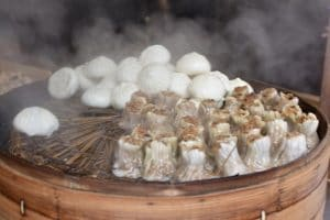 Dumplings on a bamboo basket being steamed