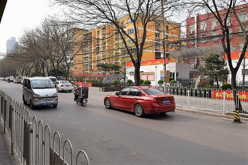 A red car driving to the left of the screen in the city of Beijing