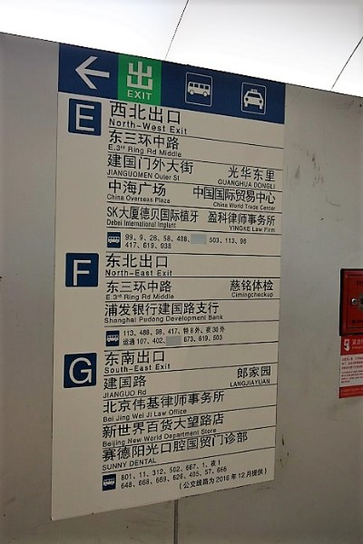 A blue and white subway sign in Beijing CBD showing the different exits of the station - Think about renting an apartment in China near a subway