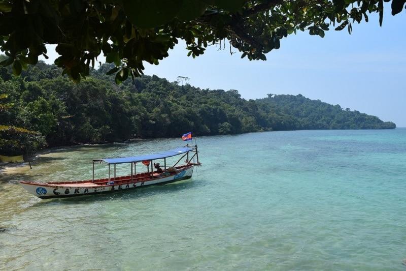 A boat anchored in a pristine island bay in the sun
