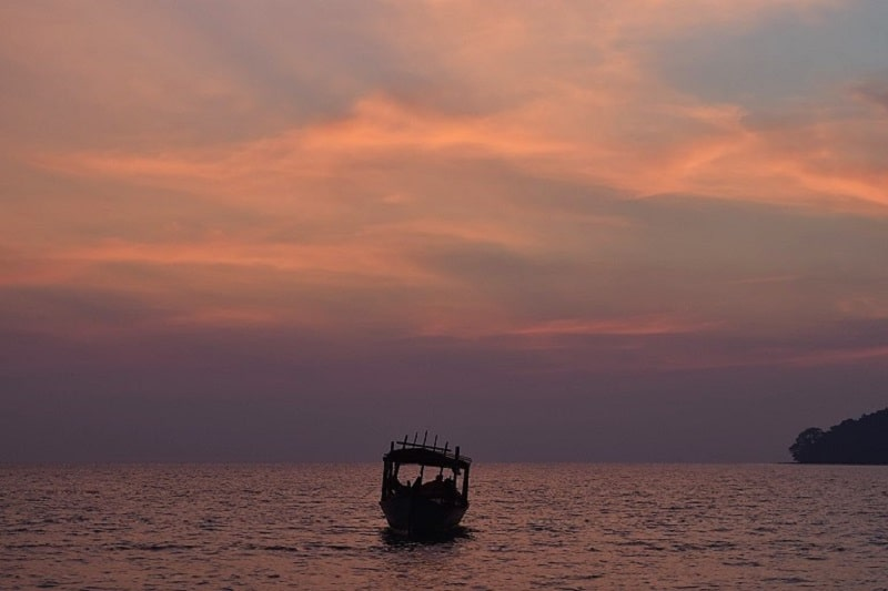 A late sunset overlooking the sea with a solitary boat drifting just off the beach