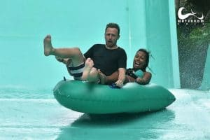 Two people looking very frightened coming down a green waterslide
