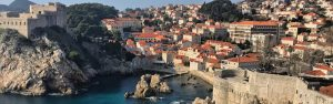 Best Places To Travel in March - A town with stone buildings and orange roofs on a cliff overlooking water