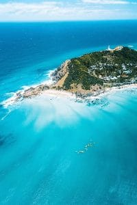 Aerial footage of an island covered in trees surrounded by aqua blue water