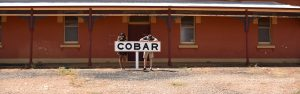 2 People leaning over a cobar sign at a railway station