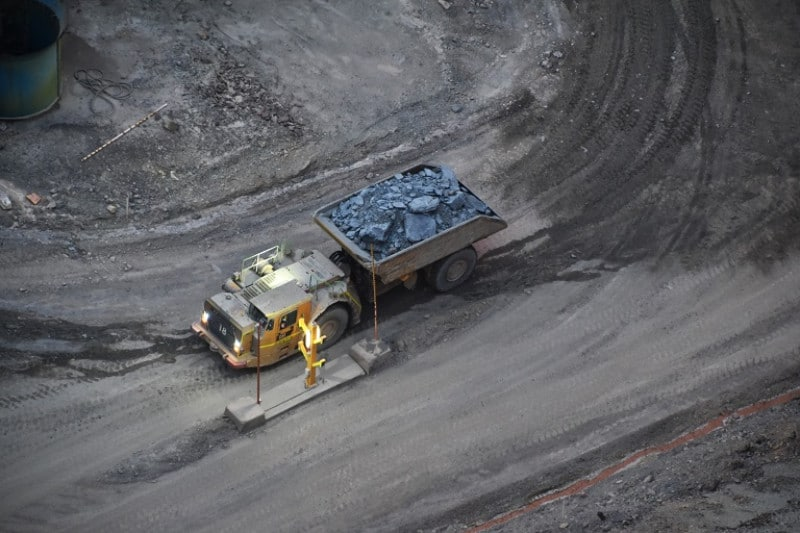 A modern very large mining truck carrying ore from an underground pit