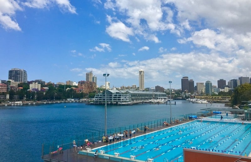 A sports swimming pool with the city and harbou in the background