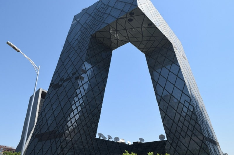 A large glass building in a unique shape that makes it look like a pair of trousers