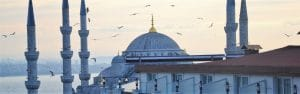 Best Places To Travel in April - White mosque with birds flying overhead