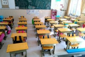 Lots of small desks and chairs aligned neatly in a classroom