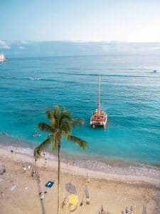 Palm trees and turquoise water with a boat