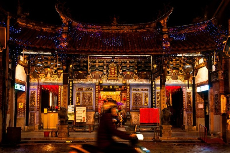 Night photo of temple with blurred motorcycle in front