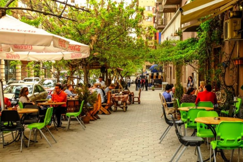 Street with cafes and chairs with people sitting outside