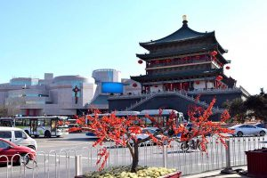 A large chinese bell tower building with red blossom in front
