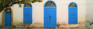 Blue doors with rounded tops in a cream wall