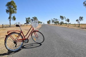 A bike on a road in the outback. Is travelling a hobby?
