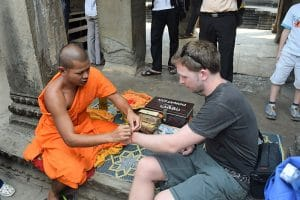 A man getting a wrist band tied on by a monk