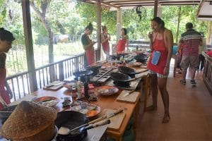 A group of people at a cooking class in Chiang Mai with a lot of cooking utensils around