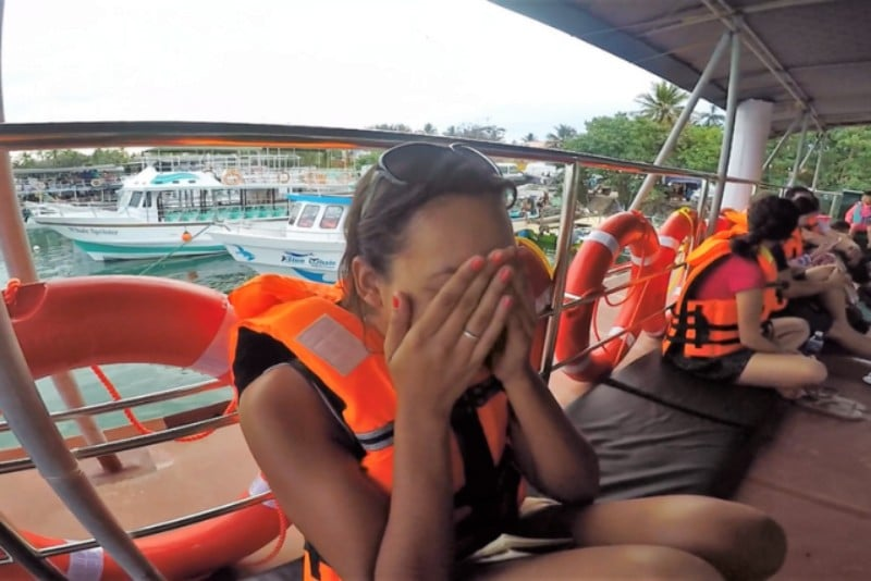 Girl wearing an orange life jacket with her hands over her face