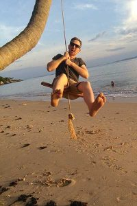 A man swinging on a swing on the beach in koh phangan