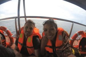 A man and a woman in orange life jackets smiling at the camera on a boat