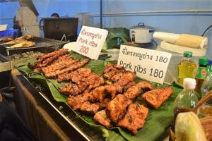 A street market stall with many different meat from a bbq on banana leaves