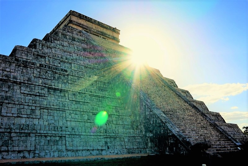 Chichan Itza - grey stone pyramind with sunlight shining over the corner