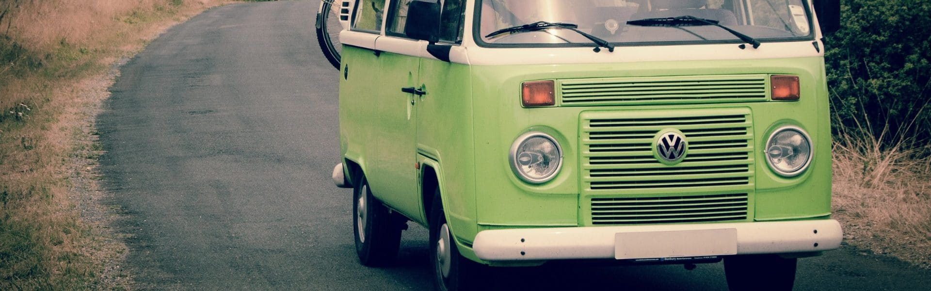 Green VW campervan driving towards the camera - 10 Fun Campervan Accessories For Your Next Road Trip