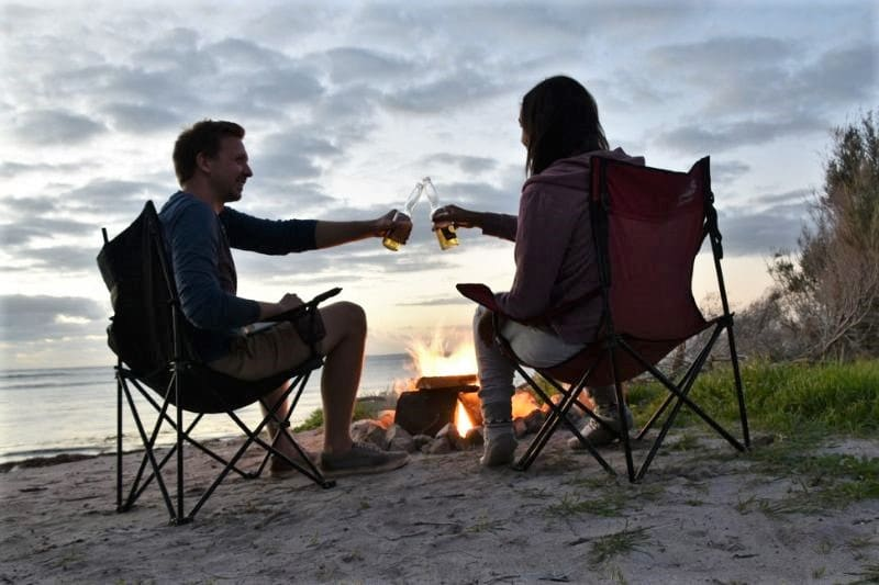 Using our fn campervan accessories on our road trip in Australia! A man and woman sitting on campchairs over a fire cheersing their beers