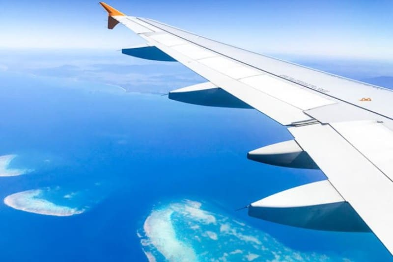 The left wing of a plane overlooking bright blue ocean